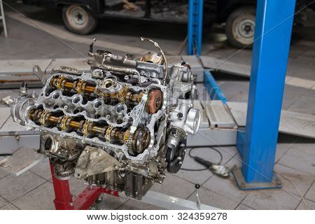 Replacement Used Engine Mounted On A Crane For Installation On A Car After A Breakdown And Repair In