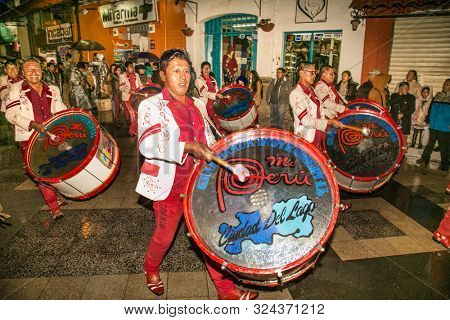 Puno, Peru - Jan 5, 2019: Musicians on authentic Colorful Carnival on the streets of Puno by night, Peru near the high altutude Titicaca lake . South America.