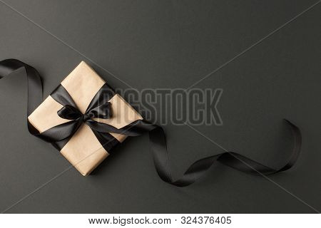 Craft Gift Box On A Dark Background, Decorated With A Textured Bow And Feathers, Creating A Romantic