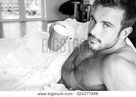 Sexy, Hairy Naked Muscular Man With Sixpack Abs Lying In Bed Covered With Sheet Drinking Coffee