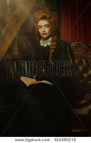 Historical reconstruction of the Victorian era. Portrait of an elegant woman in vintage  dress and hairdo reading a book in her library. Baroque era.