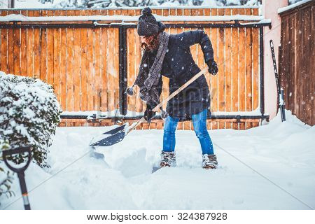 woman with shovel cleaning snow. Winter shoveling. Removing snow after blizzard