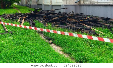 Red And White Safety Tape And Black Charred Rafters, Roof Framework On The Lawn Near The Apartment B