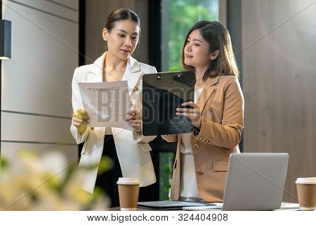Two Asian Businesswomen Discussing With The Partner Business About Business Contract By Technology L