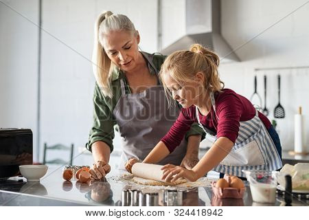 Grandmother and little girl making cookies in kitchen. Happy granddaughter with old grandma using rolling pin to flatten dough at home. Girl in apron helping senior woman to make handmade biscuits.