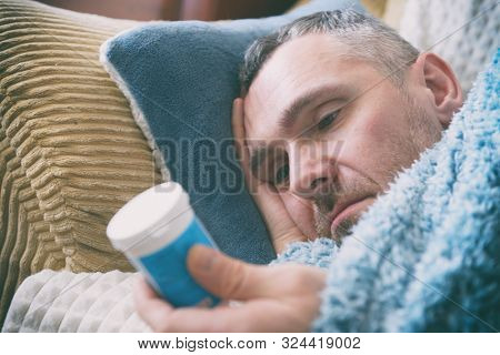 Mature man suffering from depression lies sadly covered with a blanket on his bed and looks at the antidepressants on the table poster