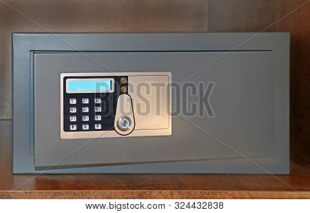 Closed Door Of Electric Safe With Digital Passcode Keypad Inside Hotel Wooden Shelf