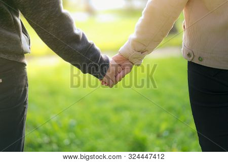 A Man Next To Woman, Guy And A Girl Are Standing Close, Touching Each Other, Holding Hands. The Conc