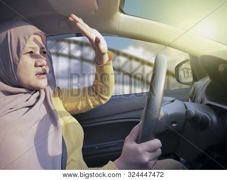 Portrait Of Asian Muslim Female Driver Get Blinded, Disturbed Dazzled By Sun Light