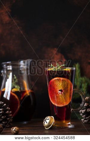 Mulled Wine A Warm Drink Made Of Red Wine, Citruses And Spices On A Wooden Table With Christmas Deco