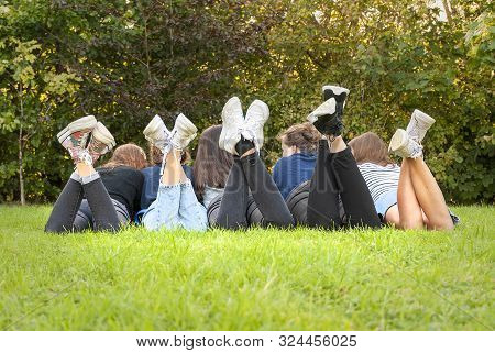 View Of The Legs And Shoes Of A Gang Of Young Teenagers Girls Standing On The Grass Of A Park. Havin