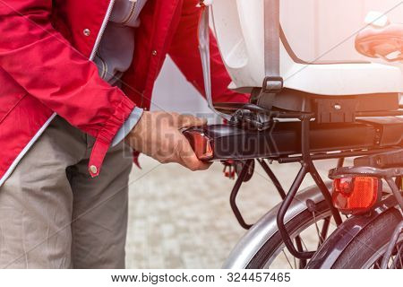 Man inserting battery in backseat of electric bicycle