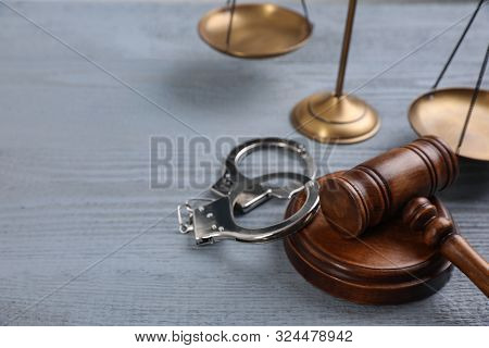 Gavel, Handcuffs And Scales Of Justice On Grey Wooden Table, Space For Text. Criminal Law