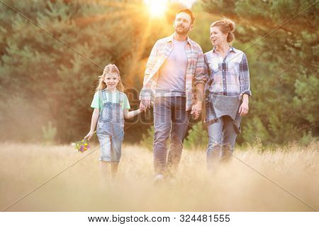 Young Caucasian family walking across field with young girl holding bouquet of flowers, concept organic ecologically friendly family