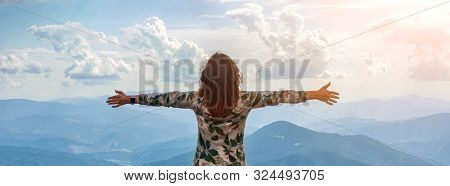 Girl Traveling In Mountains Alone, Standing With Hands Up Achieving The Top, Welcomes A Sun. Walking