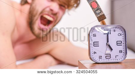 Annoying Ringing Alarm Clock. Man Bearded Annoyed Sleepy Face Lay Pillow Near Alarm Clock. Guy Knock