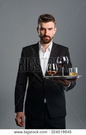 Waiter Carrying Tray With Drinks. Vertical Portrait Of Young Man Dressed In Formal Clothes With Neut