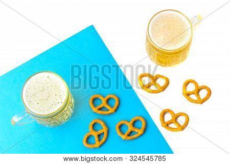 Octoberfest Concept. Beer Mug With Snacks Of Salt Pritzels, Bretzel On A White And Blue Background.