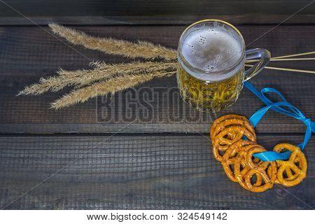 October Fest Concept. Beer Mug With Snacks Of Salt Pritzels, Bretzel And Blue Tape On A Dark Wooden