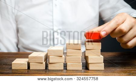 A Man Is Building A Ladder Or Growth Chart From Blocks. Strategy Planning Business Expansion. Climbi