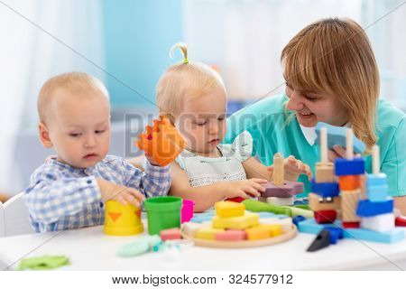 Nursery Teacher And Cute Babies Playing With Toys In Creche