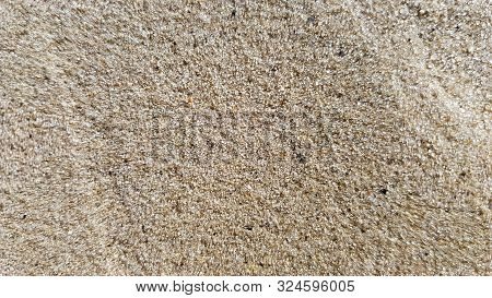 Top View Of The Sandy Beach. Background With Copy Space And Visible Sand Texture. Background Of Fine