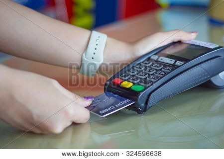 Young Woman Paying By Credit Card. Close Up Female Customer Hands Holding Credit Card And Pay On Cre