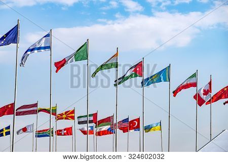 Group Of Flagstaff With International Flags Fluttering In The Wind Against On Background Of Blue Sky