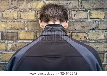 Young Man Standing With His Head Against The Wall