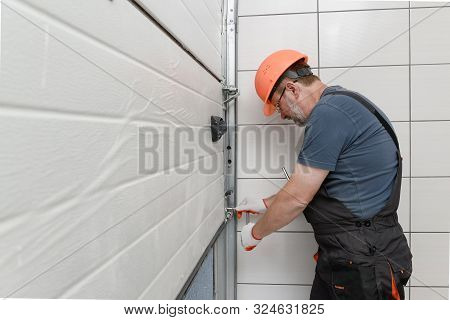 The Worker Is Installing The Lifting Gates Of The Garage.