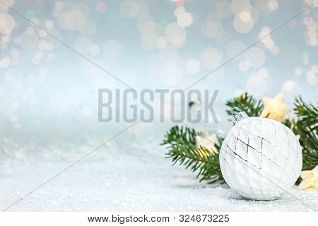Beautiful Christmas Snowy Background With Green Fir Tree Branch, White Glass Ball And Glowing Star L
