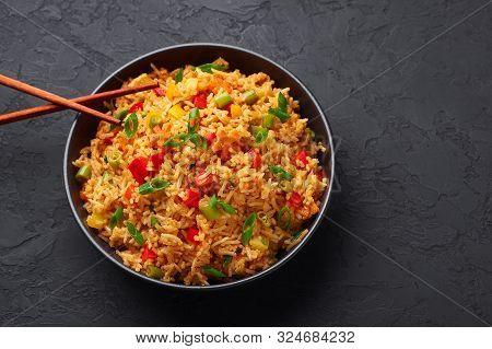 Veg Schezwan Fried Rice In Black Bowl At Dark Slate Background. Vegetarian Szechuan Rice Is Indo-chi