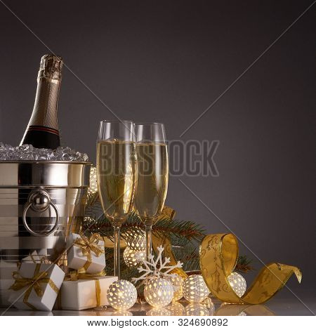 Still life with champagne bottle standing in a bucket with ice, two full champagne flutes, LED lights garland  and Christmas ornaments. Christmas and New Year celebration background