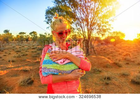 Tourist Woman Holding Orphaned Baby Kangaroo At Sunset Sunlight In Australian Outback. Interacting W