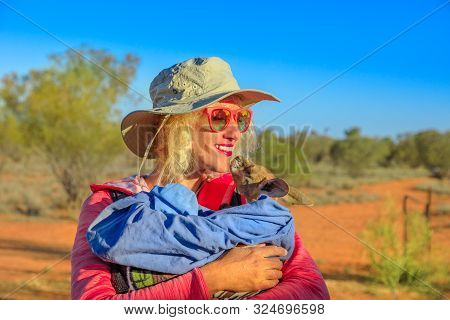 Tourist Woman Holding Orphaned Baby Kangaroo In Australian Outback, Bush Landscape. Interacting With