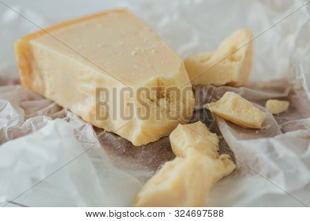 Parmesan Cheese. Delicious Italian Parmesan Cheese On White Parchment. Pieces Of Parmesan Cheese