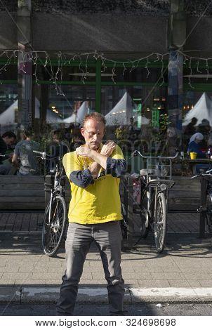 Sint Niklaas, Belgium, September 8, 2019, Man Practiced Falun Dafa, Crossing His Arms And Touch Both