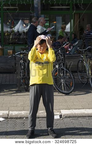 Sint Niklaas, Belgium, September 8, 2019, Oriental Woman With Hat Practiced Falun Dafa, Breathes Pow