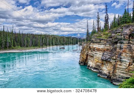 Turquoise River Athabasca Flowing Around Picturesque Rocks From The Glaciers At Summer. Jasper Natio