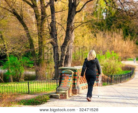 Attractive woman nordic walks in spring time
