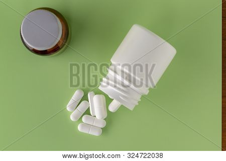 Glass And Plastic Medicine Bottles And Scattered White Drugs On A Green Background