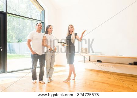 Real Estate Agent Is Selling An Apartment To A Young Family. Conclusion Of A Lease And Purchase Of A