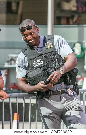 New York City, 9/27/2019: Young Smiling African American Secret Service Agent Stands At A Street Bar