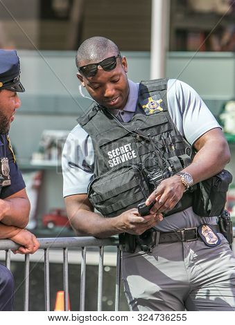 New York City, 9/27/2019: Young Secret Service Agent Is Checking His Phone At A Street Closure Durin