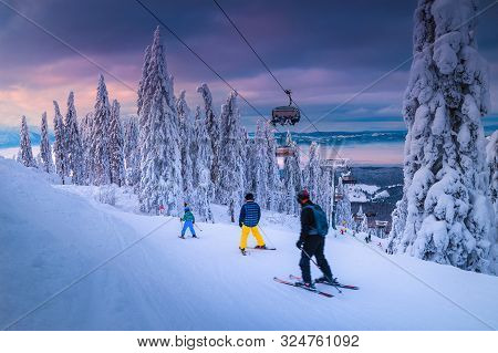 Beautiful Snow Covered Trees And Winter Ski Resort With Fast Ski Lift. Active Skiers Skiing Downhill