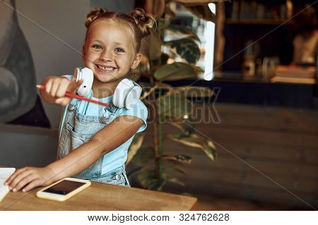 Happy Girl Pointing To The Camera And Smiling Stock Photo