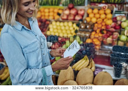 Woman Buying Food According To Her Shopping List Stock Photo