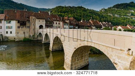 Old Stone Bridge Over A River Leads To A Picturesque Historic European Village