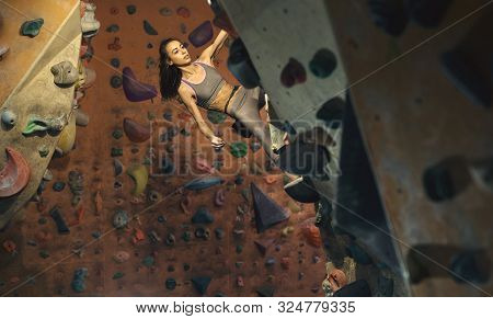 Young Female Climber Climbing Inside Climbing Gym. Slim Pretty Woman Exercising At Indoor Climbing G