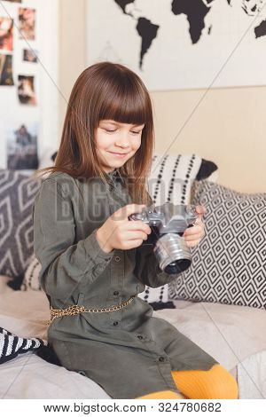 Child Girl Holding A Retro Camera Sitting On Bed At Home